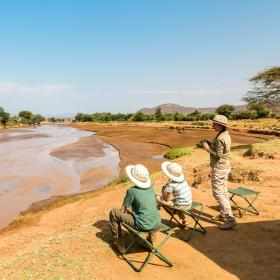 Adventurers look out over a waterhole while on safari during their Discovery Tour in Kenya.